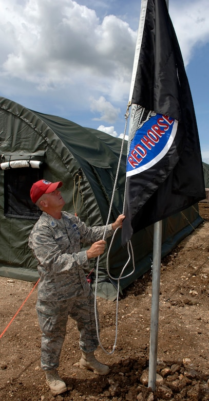 "METETI, Panama -- Senior Chief Petty Officer Shawn Crosby raises the 820th Expeditionary RED HORSE Squadron flag over the base camp housing more 250 Airmen, Soldiers, Sailors and Marines taking part in New Horizons Panama 2010, a U.S. Southern Command sponsored humanitarian assistance mission. Crosby is the ""Mayor"" of tent city, responsible for for the day-to-day functioning of the camp, including the facilities, utilities, roads and people. (U.S. Air Force photo/Tech. Sgt. Eric Petosky)"
