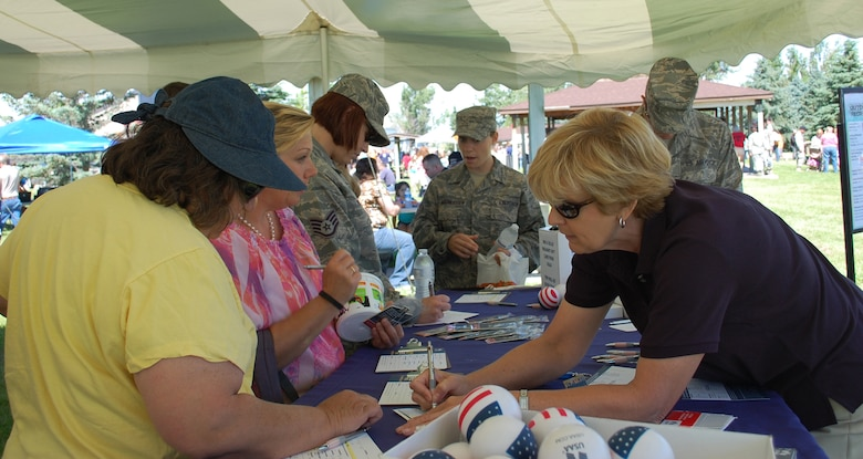 USAA representative Audrey Thompson explains some information to Joann Kiernan while other interested people look over information on the orgranization. USAA was one of the many booths on hand to give out information to those attending the free annual event July 1. (U.S. Air Force photo/Valerie Mullett)