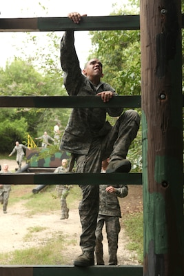 A trainee climbs an obstacle at the Air Force Basic Military Training obstacle course June 30. BMT mirrors the Air Expeditionary Force cycle -- trainees prepare to deploy, deploy to field exercises, and then reconstitute. (U.S. Air Force photo/Robbin Cresswell)