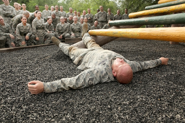 Staff Sgt. Robert Fitte, 319th Training Squadron, demonstrates how to begin an obstacle June 30. Before attempting the obstacle course, Air Force Basic Military Training trainees are briefed on proper technique and safety. (U.S. Air Force photo/Robbin Cresswell)