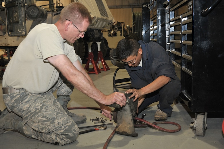 Master Sgt. Scott Listberger and Staff Sgt. Reed Nakamoto, 380th Expeditionary Logistics Readiness Squadron vehicle maintainers, work on a power steering pump bracket for a Humvee July 7 at an undisclosed location in Southwest Asia.  The maintainers are responsible for repairs and maintenance for over 230 vehicles. Sergeant Listberger is deployed from the Minnesota Air National Guard and Sergeant Nakamoto is deployed from the Hawaii Air National Guard. (U.S. Air Force photo/ Tech. Sgt. April Wickes)