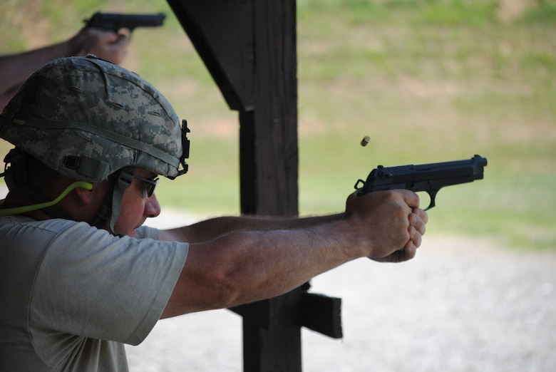 A competitor in the 2010 Tennessee National Guard shooting competition takes a kneeling firing position and fires an M-9 pistol at his target.
