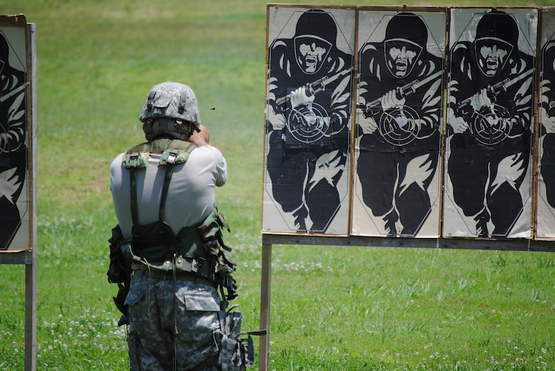 A competitor in the 2010 Tennessee National Guard shooting competition takes a standing firing position and fires an M-9 pistol at his target.