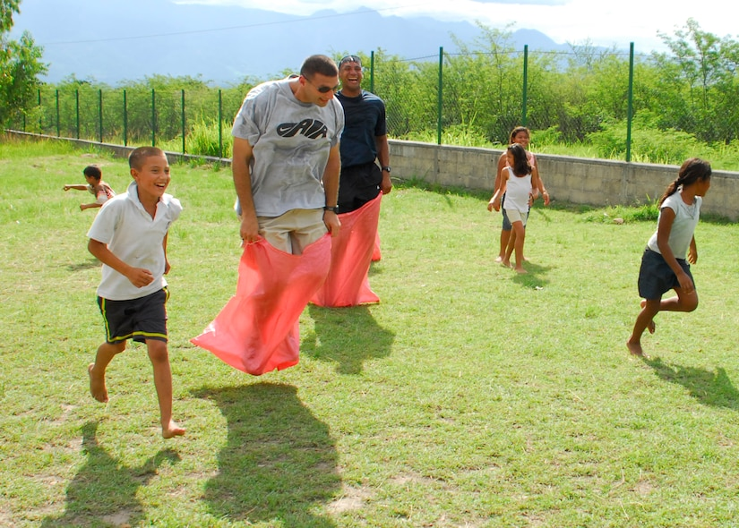 COMAYAGUA, Honduras -- Staff Sgt. Jamie Rosenthal and Tech. Sgt. Lineus Davis, both of the 612th Air Base Squadron, jump to the sack race finish line as the children of the Nuestra Señora de Guadalupe orphanage cheer them on here Friday, July 9. Other activities the 612th ABS volunteers planned for the afternoon included jump rope, soccer and tug-of-war. (U.S. Air Force photo/Tech. Sgt. Benjamin Rojek)