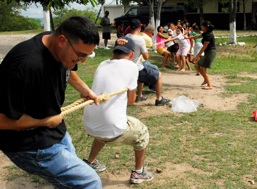 COMAYAGUA, Honduras --  Tech. Sgt. Kirk Withycombe, of the 612th Air Base Squadron, moves back with all his weight as he and three other members of the 612th ABS slowly lose ground in a tug-of-war match against 15 kids from the Nuestra Señora de Guadalupe orphanage here Friday, July 9. During their visits to the orphanage each month, the 612th ABS brings an assortment of outdoor games to play with the children. (U.S. Air Force photo/Tech. Sgt. Benjamin Rojek)