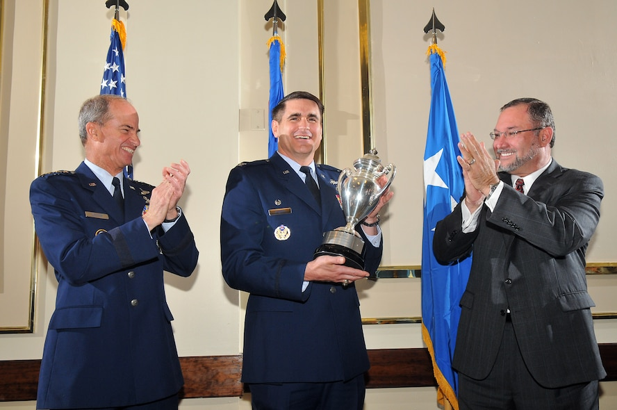 Colonel Bradford J. Shwedo, 67th Network Warfare Wing commander (center) accepts the Omaha Trophy for Global Operations on behalf of the members of the 67th NWW July 12.  Gen. Kevin P. Chilton, U.S. Strategic Command commander and Mr. Steve S. Martin, Strategic Command Consultation Committee member presented the trophy at the Kelly Club, Port San Antonio. The Omaha Trophy is awarded annually to four military units demonstrating the highest performance standards in U.S. Strategic Command mission areas, according to the command. (U.S. Air Force photo by Ted Koniares)