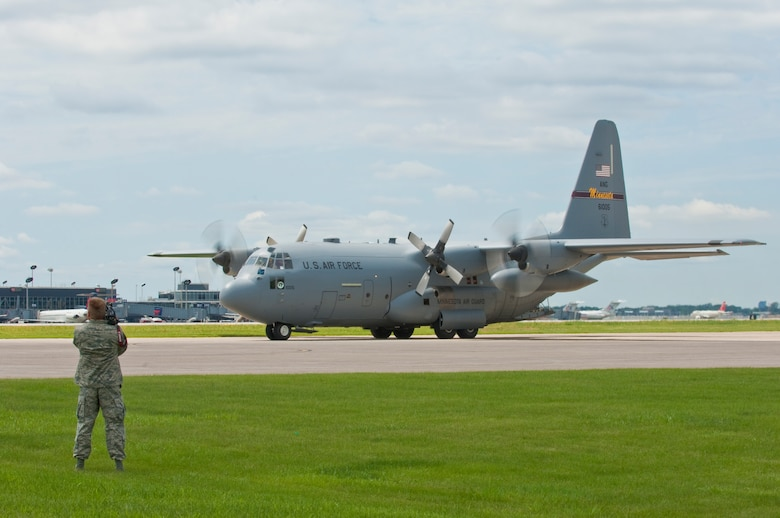 """A  C-130 """"Hercules"""" taxis into position for recovery at the Minneapolis-St. Paul International airport on July 11, 2010 after returning from a tour in Afghanistan. The military cargo aircraft and about twenty Airmen are the first in a series of returns during July for the 133rd Airlift Wing in 2010. USAF official photo by Senior Master Sgt. Mark Moss"""