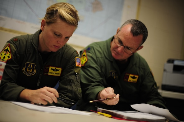 U.S. Air Force Maj. Jenette Jensen (left) and Lt. Col Daryl Humphrey, both KC-135 Stratotanker pilots assigned to the 465th Air Refueling Squadron, Tinker Air Force Base, Okla., review flight information before a refueling mission during exercise Rim of the Pacific (RIMPAC) at Joint Base Pearl Harbor Hickam, Hawaii, July 9, 2010.  during exercise Rim of the Pacific (RIMPAC) at Joint Base Pearl Harbor Hickam, Hawaii, July 9, 2010.  RIMPAC 2010 is the 22nd in a series of significant international combined/joint military exercises scheduled biennially by U.S. Pacific Fleet and takes place in the Hawaiian operating area.  RIMPAC training operations include participation by more than 14 nations, 34 ships, five submarines, more than 100 aircraft, and more than 20,000 Soldiers, Sailors, Marines and Airmen.  Multilateral exercises such as RIMPAC enhance cooperation between partnering nations and provide a unique opportunity to practice the ability to plan, communicate, and execute operations.  (U.S. Air Force photo by Tech. Sgt. Jacob N. Bailey/Released)