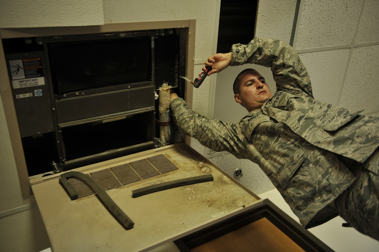 MOODY AIR FORCE BASE, Ga.-- Senior Airman Steven Kindle, 23rd Civil Engineer Squadron heating, ventilation, air conditioning and refrigeration journeyman, cleans out a drain line in a dormitory room here July 7.  The drain line requires cleaning because air condition units leak due to sludge build up. (U.S. Air Force photo by Staff Sgt. Schelli Jones/RELEASED)