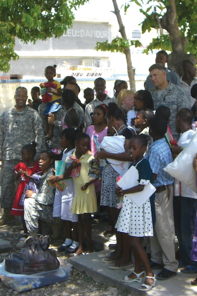 HAITI - Lt. Col. Kevin K. Callies, 114th Fighter Wing comptroller, and his staff are surrounded by many of the local children they are deployed to help in Haiti when they visited an orphanage there on May 16.  The children surrounded the military members and began to sing Hallelujah upon seeing the task force members arrive. (Photographer unknown - released)