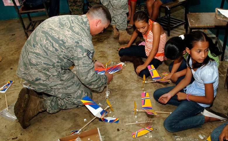 Staff Sgt. Josh Lazarski, 820th Expeditionary RED HORSE Squadron, helps children assemble rubber band airplanes at the Sansonsito School July 12. (U.S. Air Force photo/Tech. Sgt. Eric Petosky)