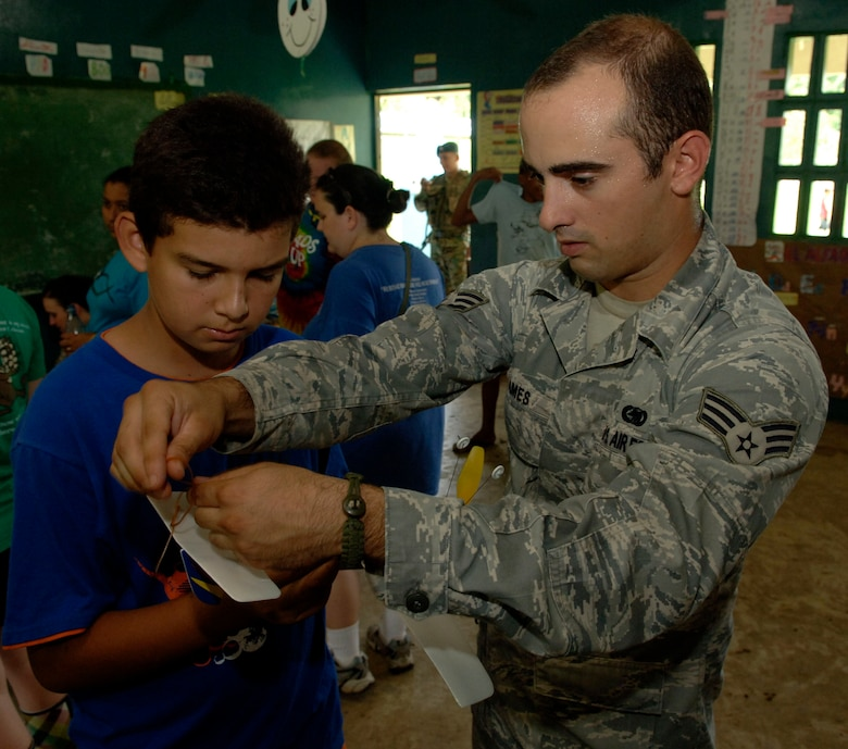 Senior Airman Alex James, 820th Expeditionary RED HORSE Squadron, helps children assemble rubber band airplanes at the Sansonsito School July 12. (U.S. Air Force photo/Tech. Sgt. Eric Petosky)