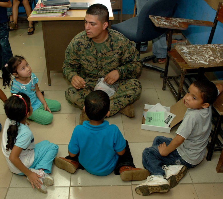 Lance Cpl. Carlos Fuentes, a civil affairs Marine deployed from the 4th Civil Affairs Group, helps children assemble rubber band airplanes at the Sansonsito School July 12. (U.S. Air Force photo/Tech. Sgt. Eric Petosky)