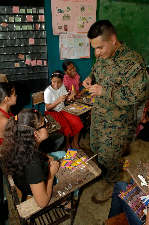 Pfc. Juan Romero, a civil affairs Marine deployed from the 4th Civil Affairs Group, helps children assemble rubber band airplanes at the Sansonsito School July 12. (U.S. Air Force photo/Tech. Sgt. Eric Petosky)