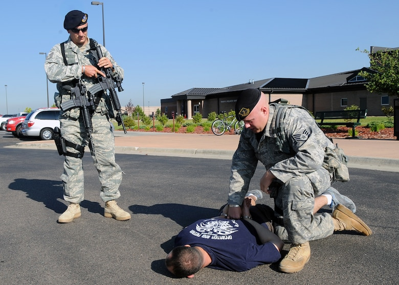 Buckley Air Force Base, Colo.- Buckley's Exercise Evaluation Team gears up testing Buckley's emergency response procedures. Ssgt Christopher Allen and Ssgt Vondor subdue and restrain a robbery suspect at Buckley's Fitness Center.  ( U.S. Air Force Photo by Airman First Class Marcy Glass )
