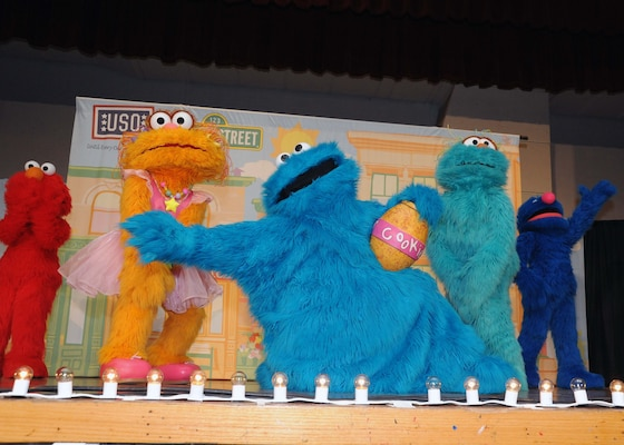 Cookie Monster and his friends perform on stage during the USO sponsored Sesame Street Experience July 8 at the Bob Hope Performing Arts Center. (U.S. Air Force photo/Alan Boedeker)