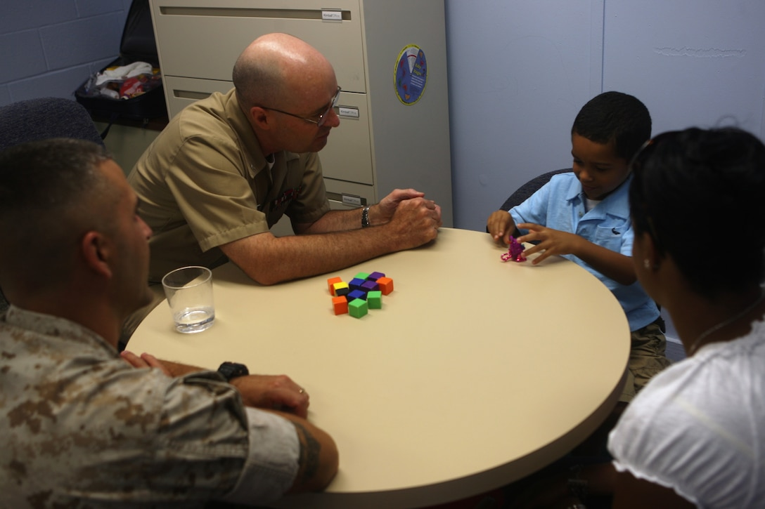 Navy Capt. Joseph McBreen, medical consultant for the Marine Corps Base Camp Lejeune Educational and Developmental Intervention Services, sits down with a family at the Berkeley Manor Naval Hospital Annex, recently. The EDIS program, following the Exceptional Family Member Program, assists family members in diagnosing their childrens' possible handicap while also providing treatment and any medicine that may be necessary at no expense to the family.