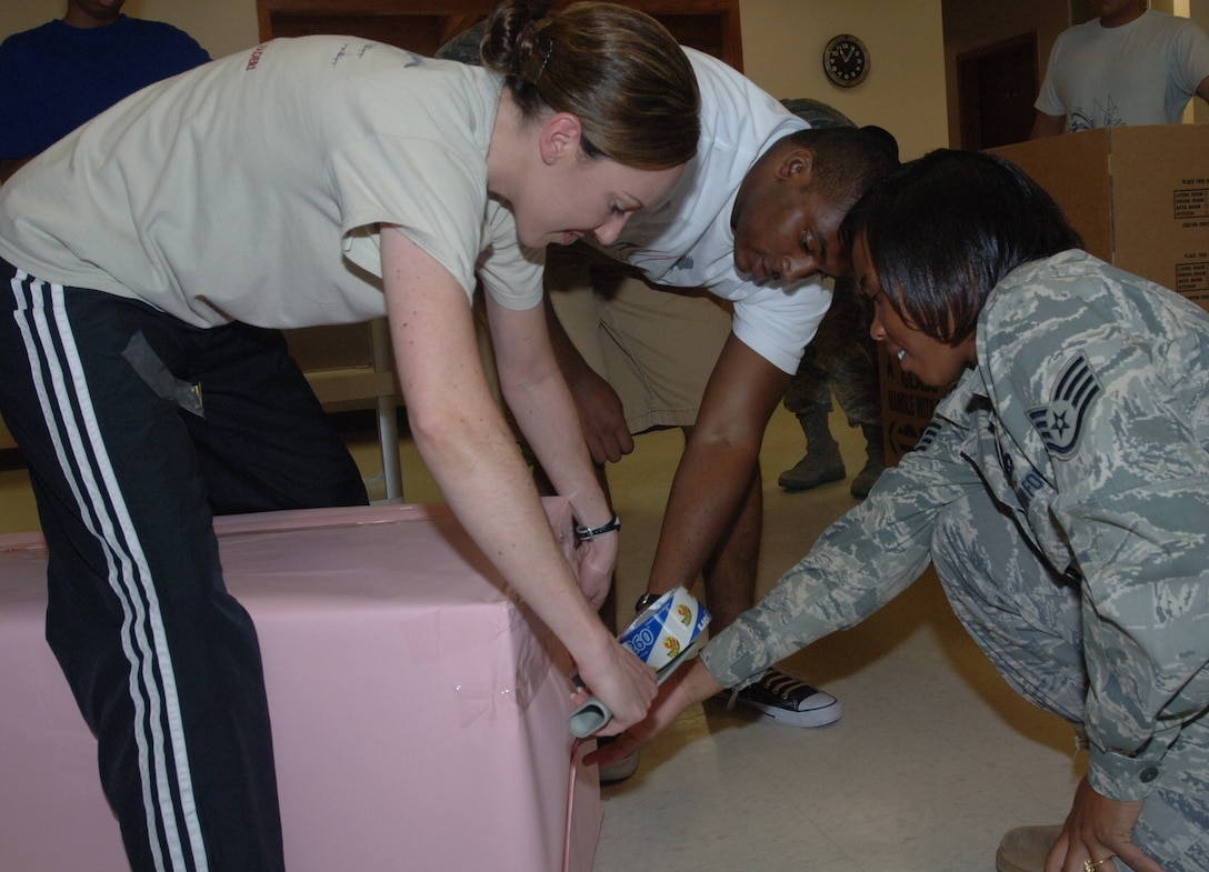 Tech. Sgt. Kelly Rodriguez (left), 319th Operations Support Squadron, Airman 1st Class Marshall Merriweather (middle), 319th Logistics Readiness Squadron and Staff Sgt. Krystal Thompson (right), 319th Civil Engineer Squadron, make donations boxes for the Salvation Army July 16. The group of Grand Forks Air Force Base volunteers unloaded 10,104 pounds of food worth over $1,200. Network 5/6 organizes volunteers the third Friday of every month to help unload and stock food for the food bank at the Salvation Army in Grand Forks, N.D.