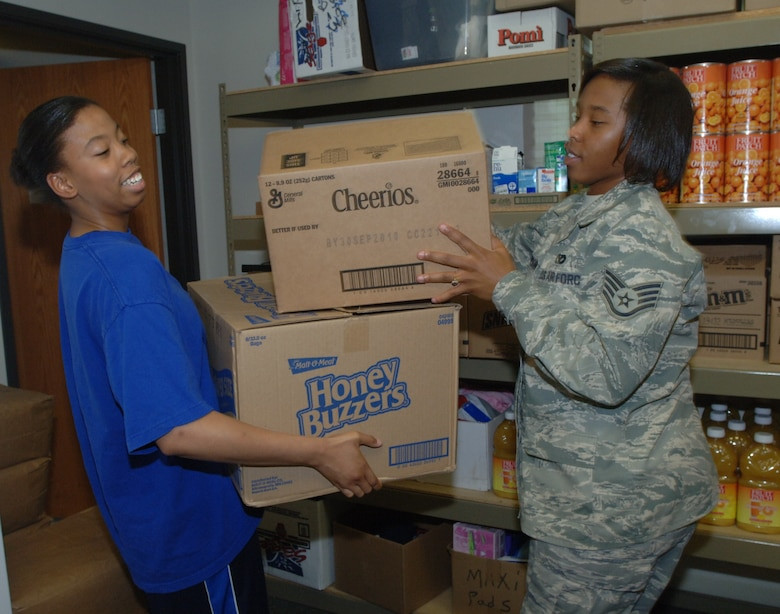 Airman 1st Class Anna Moreland (left), 319th Communications Squadron, and Staff Sgt. Krystal Thompson, 319th Civil Engineer Squadron, begin stocking and organizing the 10,104 pounds of food that Grand Forks Air Force Base volunteers unloaded for the Salvation Army July 16. Network 5/6 organizes volunteers the third Friday of every month to help unload and stock food for the food bank at the Salvation Army in Grand Forks, N.D.