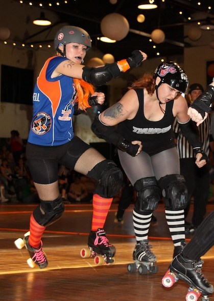 Long-distance runner Jamie Weber, left, was looking to change up her workout routine when she attended her first roller derby bout. Though she's just playing in her first year, the engineer with the 72nd Air Base Wing Civil Engineering Directorate, has a reputation as one of the best jammers on her team. (Courtesy photo)
