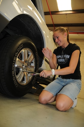 "Patricia Annunziata, Marine Attack Squadron 211 spouse, takes the lug nuts off a tire as she prepares to replace it during a vehicle maintenance class in the auto hobby shop at the Marine Corps Air Station in Yuma, Ariz., July 16, 2010. The class is the first in a series of educational blocks designed to help squadron spouses become more self-sufficient when their Marines are deployed overseas. ""It was very scary,"" said  Annunziata of her first deployment experience. ""I didn't know anything. (The class) was great, it had a lot of great information."""