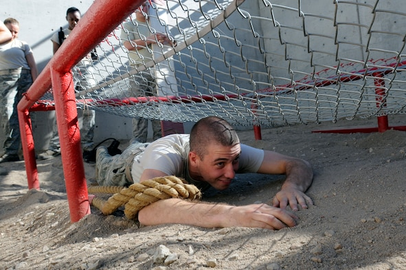 Basic Cadet Alexander Pecci III crawls through an obstacle at the Leadership Reaction Course in Jacks Valley during Basic Cadet Training at the U.S. Air Force Academy July 16, 2010. The Leadership Reaction Course teaches basic cadets group and individual problem solving and effective leadership by having them work through 15 obstacles of varying difficulty. (U.S. Air Force photo/J. Rachel Spencer)