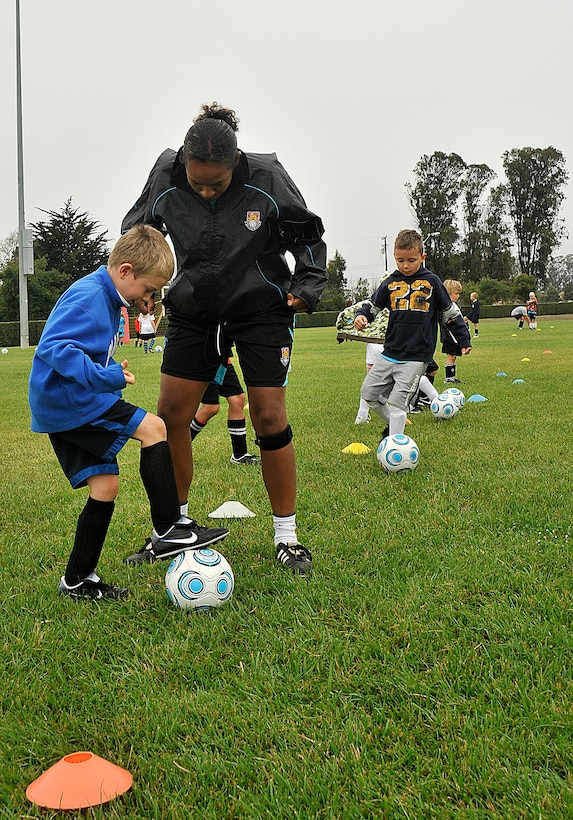 VANDNEBERG AIR FORCE BASE, Calif.-- European soccer coach Chantelle Miller,  with Challenge Sports, teaches William Fernengel, son of Capt. Christopher Fernengel, of the 14th Air Force, how to stop the ball here, Tuesday, July 20, 2010. Challenge Sports is hosting their annual soccer camp at Vandenberg this week. (U.S. Air Force Photo/Senior Airman Stephanie Longoria)