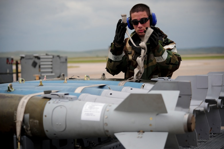 ELLSWORTH AIR FORCE BASE, S.D. – Airman 1st Class Alejandro Sanchez, 28th Munitions Squadron weapons loader, straps down guided bomb unit-38s during the phase II operational readiness exercise, July 21. The GBU-38 is a 500-pound bomb commonly used with the B-1B Lancer.  (U.S. Air Force photo/Airman 1st Class Corey Hook)