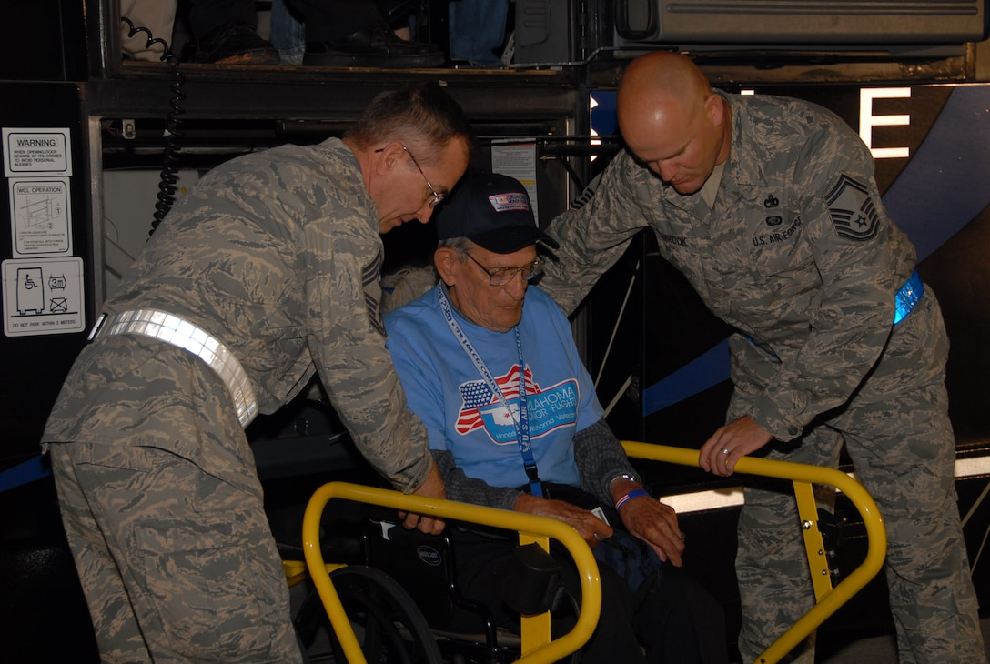 Senior Master Sgt. Stephen Rosebrook and Chief Master Sgt. Steven Keene, both assigned to the 137th Logistics Readiness Squadron, help a veteran onto an airplane on the base flight line.  Veterans who were wheelchair bound were given the royal treatment as they were lifted off the bus and carried onto the charted flight to Washington, D.C. and the World War II Memorial.