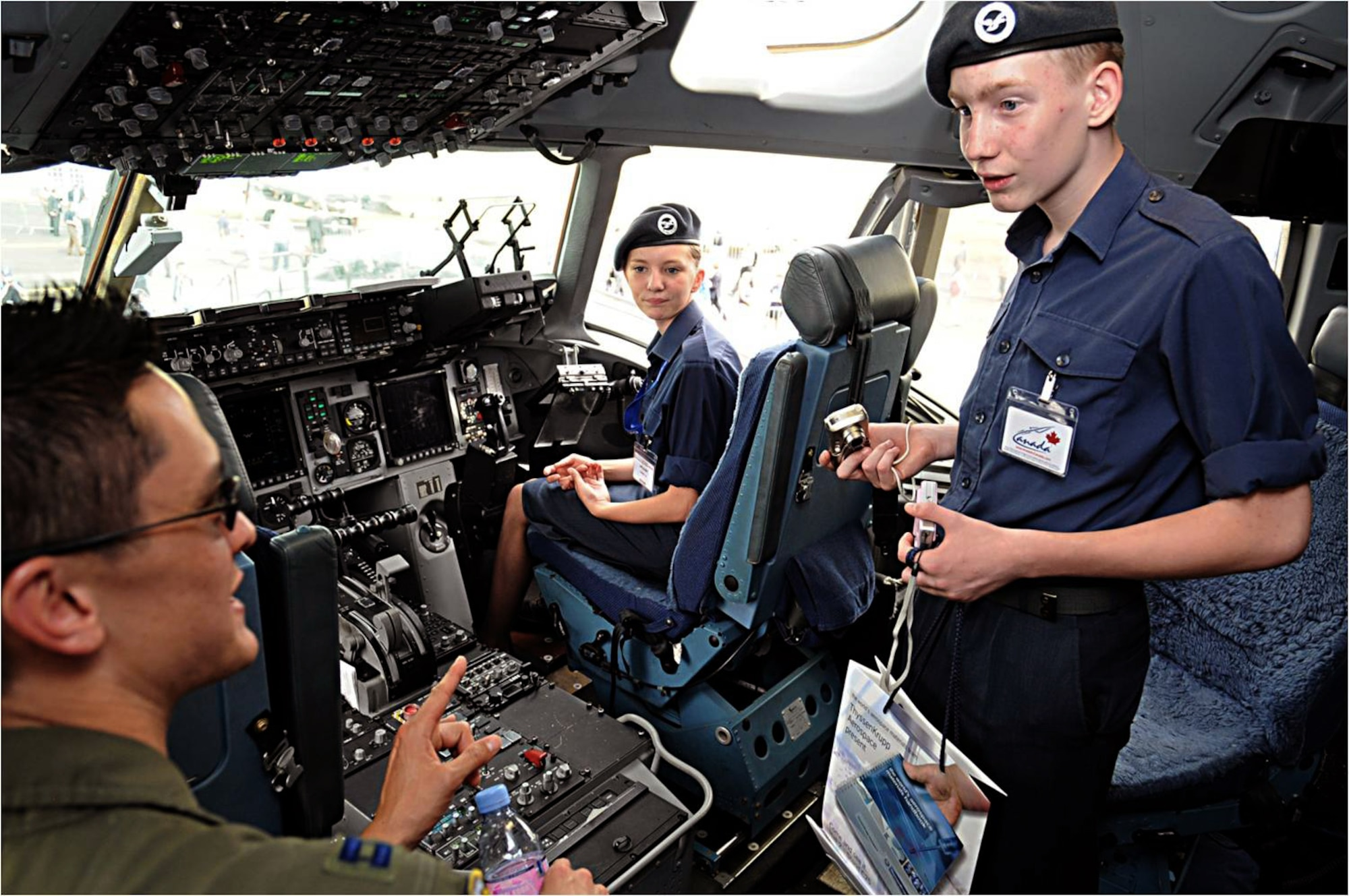 Capt. Gordon Roman (left) explains cockpit controls to British cadets July 20, 2010, in Farnborough, England. Eleven U.S. military aircraft and approximately 70 personnel representing all branches of service participate in the 2010 Farnborough International Air Show.  Captain Roman is a C-17 Globemaster III pilot from Travis Air Force Base, Calif. (U.S. Air Force photo/Staff Sgt. Jerry Fleshman)