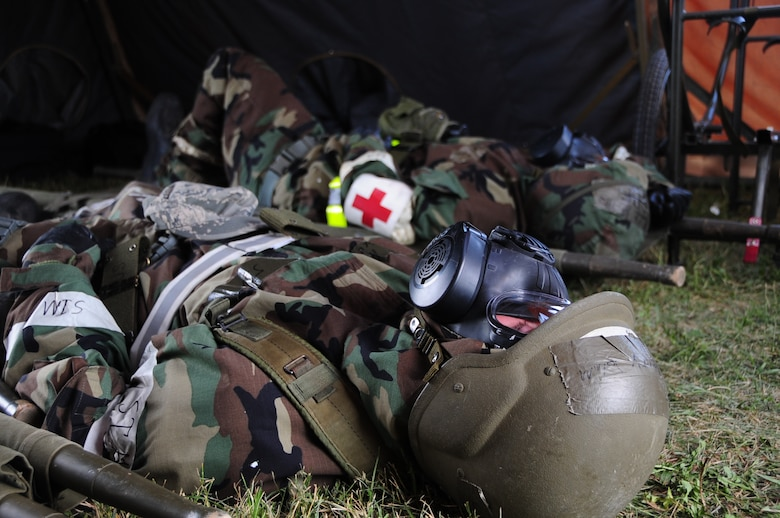 ELLSWORTH AIR FORCE BASE, S.D. -- (Back to front) Airmen 1st Class Julie Kemps, 28th Medical Operations Squadron flight medicine technician, and John Henry, 28 MDOS ambulance services technician, take cover in a simulated bunker while wearing mission-oriented protective posture gear during a phase II operational readiness exercise, July 21.  The MOPP gear is designed to protect Airmen in case of a chemical or biological-based attack. (U.S. Air Force photo/Airman 1st Class Anthony Sanchelli)
