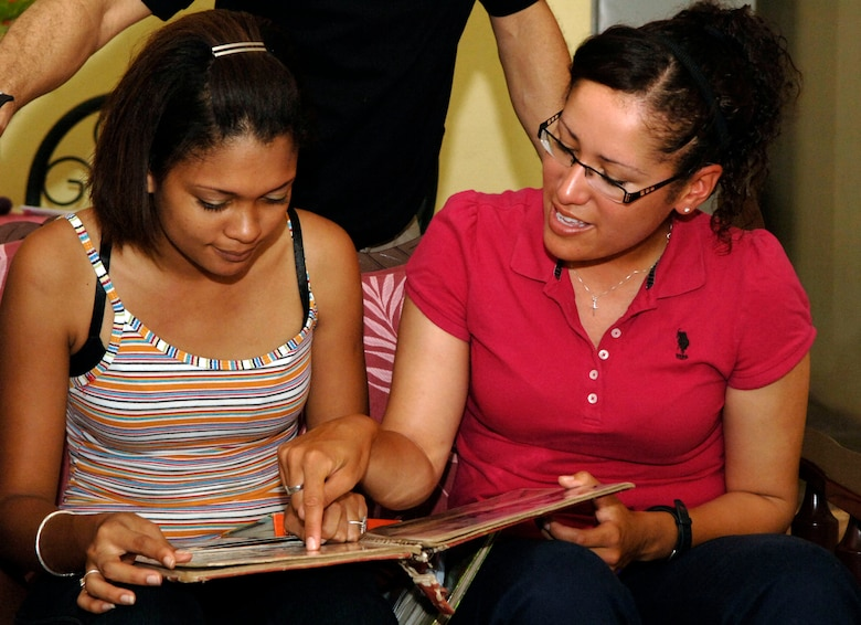 """Senior Airman Sheryl Job (right) scours photo albums with her cousin and childhood playmate, """"Princess"""" Sepulveda June 11 in Felippio, Panama. The 25-year-old Panamanian native deployed from the 119th Wing in Fargo, N.D., to support New Horizons Panama 2010, and she was able to visit members of her family whom she had been separated from for 18 years."""