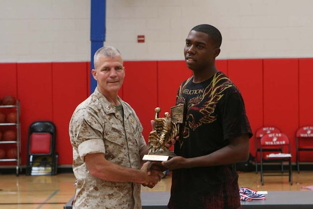 Col. Frank A. Richie, the commanding officer of Marine Corps Air Station Miramar in San Diego, awards the most valuable basketball player title to Christopher Harris, small forward, July 23, 2010, after the Marine Corps West Coast Regional Tournament. Harris, with the Marine Corps Air Station in Yuma, Ariz., was named to the all-tournament team along with other Yuma players. The team finished third overall, losing to Miramar in the first elimination round July 22, 2010.
