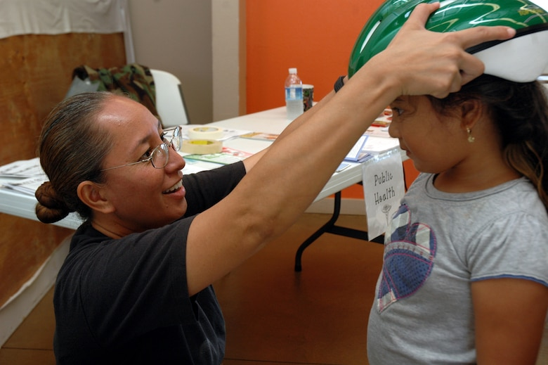 Capt. Elzadia Kainae, 154th Medical Group, clinical nurse, measures a bike helmet on a young child during the Innovative Readiness Training, July 16, in Waianae, Hawaii.  Innovative Readiness Training is an opportunity for Guard members to complete training while performing free medical services to the community. (U.S. Air Force photo/Tech. Sgt. Betty J. Squatrito-Martin)