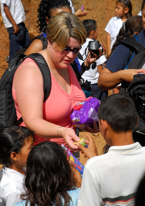 EL ROBLITO, Honduras --  While the parents wait in line for food and clothes, Master Sgt. Danielle McClarin, of Joint Task Force-Bravo, hands candy to their children during the Chapel Hike here July 16. More than 50 JTF-Bravo members hiked to this remote mountain village to hand out food, clothes and other supplies to families in need. (U.S. Air Force photo/Tech. Sgt. Benjamin Rojek)