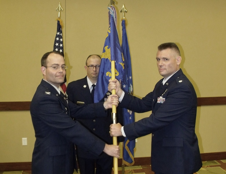 Lt. Col. Brian Denman, incoming 39th Information Operations Squadron commander, receives the 39 IOS guidon from Col. Michael Convertino, 318th Information Operations Group commander, during a change of command ceremony July 20.   Lt. Col. Dean Clothier relinquished command after leading the Air Force's information operations and cyber formal training unit for two years. (US Air Force photo)