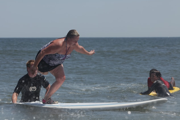 Tara Hutchinson surfs during the Long Beach Waterfront Warriors beach day, July 26, Long Beach, N.Y. She is one of 34 service members the Long Beach Waterfront Warriors has brought to New York for a week-long respite for families going through the long process of recovering from war injuries. Hutchinson has spent the last four years undergoing countless surgeries as she recovers from having her leg amputated. (Official Marine Corps photo by Sgt Randall A Clinton / RELEASED)