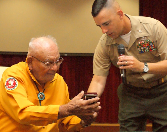 Keith Little, a Navajo who served in the Marine Corps during World War II, receives a gift from Colonel Alan Pratt, Marine Corps Tactical Systems Support Activity's (MCTSSA) Commanding Officer, at MCTSSA's Acquisition Excellence Day.
