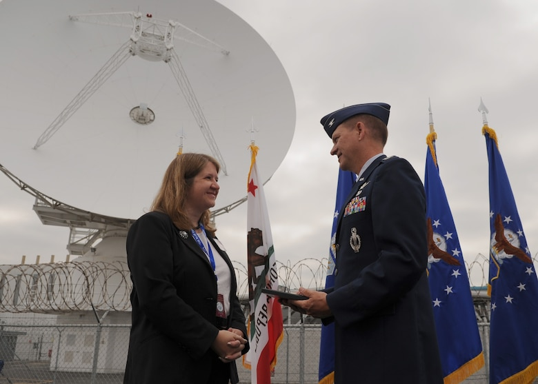 SUNNYVALE, Calif.-- Col. Wayne Monteith, the 50th Space Wing commander, presents a commemorative plaque to Mayor Melinda Hamilton during the Onizuka Air Force Station closure ceremony here, Wednesday, July 28, 2010. Built in 1960, Onizuka AFS was originally known as the Air Force Satellite Test Center. It was selected for closure by the Base Closure and Realignment Commission in 2005, with the recommendation to move operations to Vandenberg Air Force Base, in order to consolidate satellite command and control operations while reducing excess infrastructure. (U.S. Air Force Photo/Senior Airman Bryan Boyette)