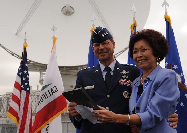 SUNNYVALE, Calif.-- Lt. Gen. John T. Sheridan, commander of the Space and Missile Center, Los Angeles Air Force Base, presents Lorna Onizuka, widow of Col. Ellison Onizuka, astronaut aboard the Space Shuttle Challenger disaster, with a commemorative plaque during a closure ceremony for Onizuka Air Force Station here, Wednesday, July 28, 2010. Built in 1960, Onizuka AFS was originally known as the Air Force Satellite Test Center. It was selected for closure by the Base Closure and Realignment Commission in 2005, with the recommendation to move operations to Vandenberg Air Force Base, in order to consolidate satellite command and control operations while reducing excess infrastructure.  (U.S. Air Force Photo/Senior Airman Bryan Boyette)