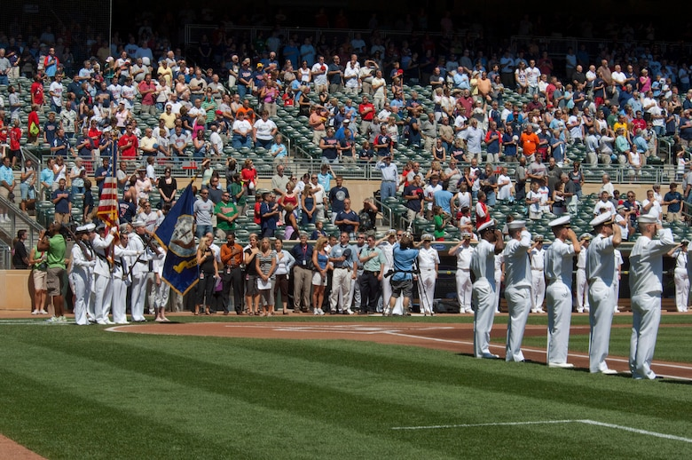 """U. S. Navy Reserve Sailors based in Minnesota stand along the baselines while an honor guard presents the colors during the national anthem at the beginning of a Minnesota Twins game at Target Field on July 21, 2010. Overhead, after jumping out of a 133rd Airlift Wing C-130, the U. S. Navy parachute team """"Leap Frogs"""" trail smoke and bring the game ball. The Minnesota Twins are celebrating Navy Day in their new stadium. The Air National Guard crew is joined by aviators from the 934th Airlift Wing, U. S. Air Force Reserve supporting this event.  USAF official photo by Senior Master Sgt. Mark Moss"""
