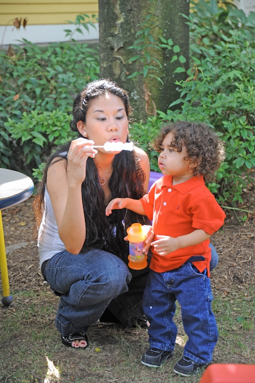 Julie and Genghis Webb blow bubbles in the backyard of the Ronald McDonald House July 20, 2010, in New Haven, Conn. The Webb family has been staying at the Ronald McDonald House following Genghis liver transplant surgery in April, when his father, Senior Airman Mario Webb, donated 20 percent of his liver to his son. Airman Webb is assigned to the 23rd Special Tactics Squadron at Hurlburt Field, Fla. (U.S. Air Force photo/Staff Sgt. Mareshah Haynes)