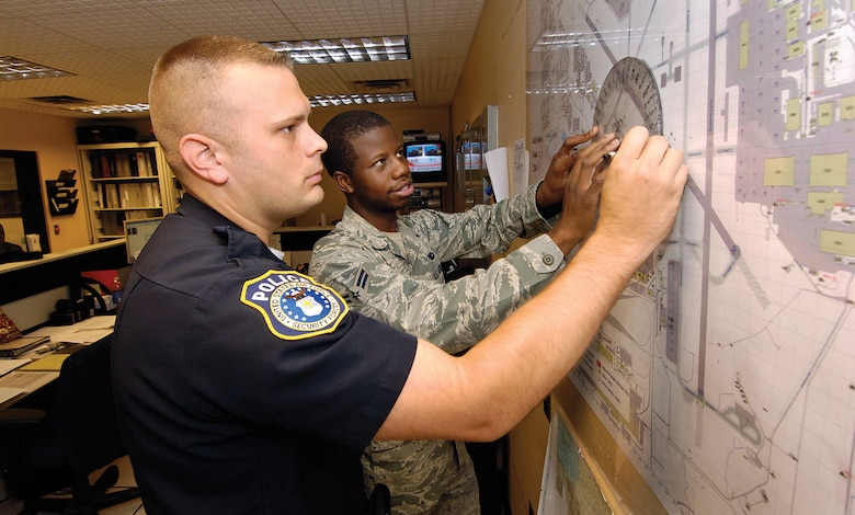 In the 72nd Security Forces Squadron's Base Defense Operations Center, as all across base, military security forces work beside the DOD police officers.  Airman 1st Class Jonathan White and Officer Smith practice plotting a cordoned area as they would during a real-world emergency or an exercise. (Air Force photos by Margo Wright)
