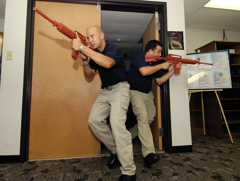 A team of new police officers, including Seth Ryan, left, and Brent Huddleston, burst into a room during an active-shooter scenario training session on base.  In more than 120 hours of initial training, the new officers will learn how to respond to domestic violence and child abuse situations, community oriented policing and use of force. (Air Force photos by Margo Wright)