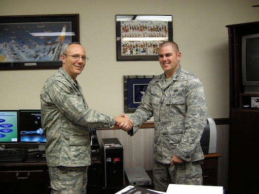 Col. Robert L. Maness, left, 377th Air Base Wing commander, presents a coin July 15 to Capt. Peter C. Talley, 377th Comptroller Squadron, for his development of the FM desktop reference.  U.S. Air Force photo by Marie Vanover.