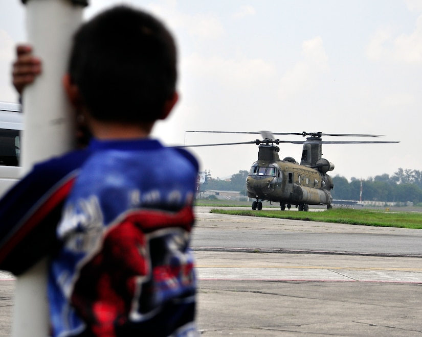 A young boy watches a CH-47 Chinook taxi away at the Guatemala City Airport after dropping off Joint Task Force-Bravo personnel June 1. At the request of the Guatemalan government, U.S. Southern Command's Joint Task Force-Bravo deployed four helicopters and more than forty personnel from Soto Cano Air Base, Honduras, to support humanitarian assistance efforts in Guatemala following Tropical Storm Agatha. (U.S. Air Force photo by Staff Sgt. Bryan Franks)