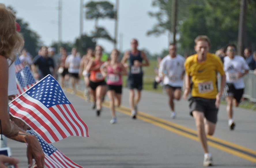 Supporters wave flags and cheer on runners as they approach the finish line during the 4.4 mile Gate-to-Gate run/walk held annually on Memorial Day at Eglin Air Force Base, Fla.  (U.S. Air Force photo/Staff Sgt. Stacia Zachary)