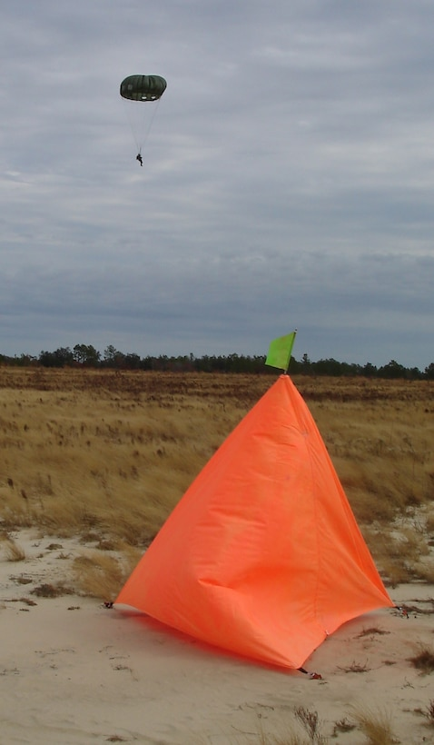 An unidentified parachutist floats next to the desired point of impact within the raised angle markers set by the 1st Special Operations Support Squadron Range Support flight Assault Zone team at an undisclosed location in the Eglin Range, Fla., Dec. 12, 2006. The Assault Zone team members draw on their combined experiences of more than 60 years in the field to assist Range Support clientele to successfully attain their Mission Essential Task Lists. (Courtesy photo)