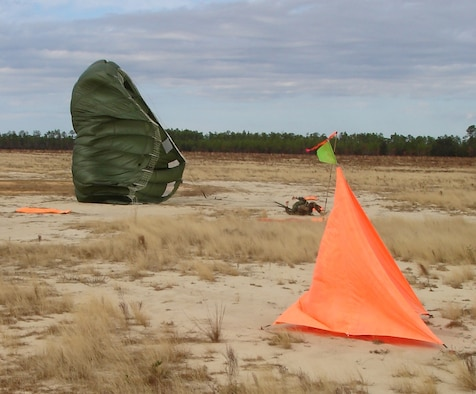 An unidentified parachutist lands next to the desired point of impact within the raised angle markers set by the 1st Special Operations Support Squadron Range Support flight Assault Zone team at an undisclosed location in the Eglin Range, Fla., Dec. 12, 2006. The Assault Zone team members draw on their combined experiences of more than 60 years in the field to assist Range Support clientele to successfully attain their Mission Essential Task Lists. (Courtesy photo)