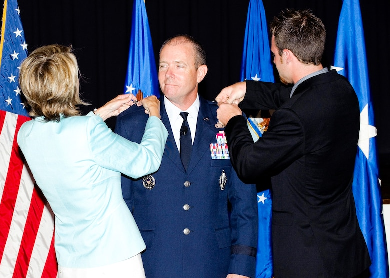 Brigadier General Kevin Jacobsen (center) has his stars pinned on by his wife Karen (left) and son Steven (right). (U.S. Air Force photo/Mike Hastings)